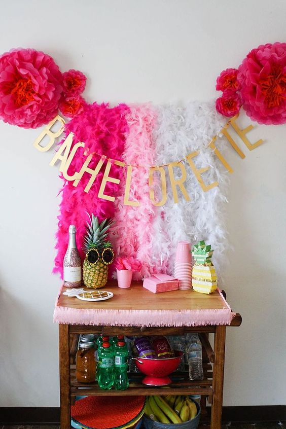 a tropical bachelorette bar cart styled with natural and fake pineapples and lush pink garlands over it