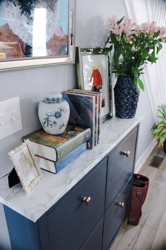 glam up your IKEA Hemnes shoe cabinet with navy paint and some marble contact paper plus brass knobs to get a stylish look