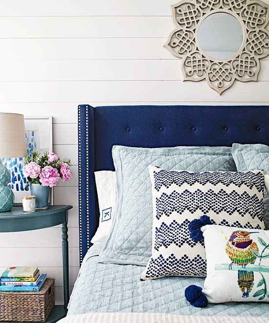 a bold blue wingback headboard with a nail trim and bright printed pillows make up a chic look