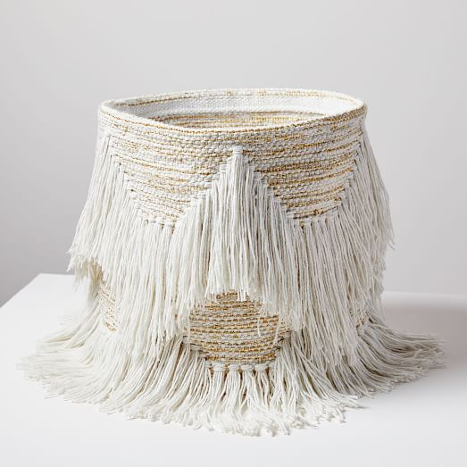 a soft fringe basket in neutrals is a very cool and whimsy idea for storage
