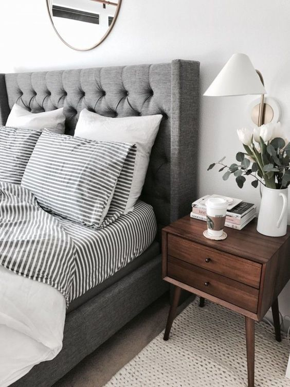 a grey upholstered bed with a wingback headboard and grey bedding is a very relaxing and calming idea