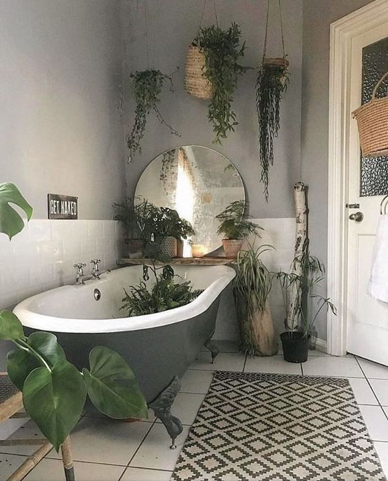 hanging potted greenery and some plants by the bathtub and in it for a fresh feel