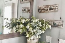 23 spring bathroom decor with a lush floral centerpiece and succulents in a pot plus a woven tray