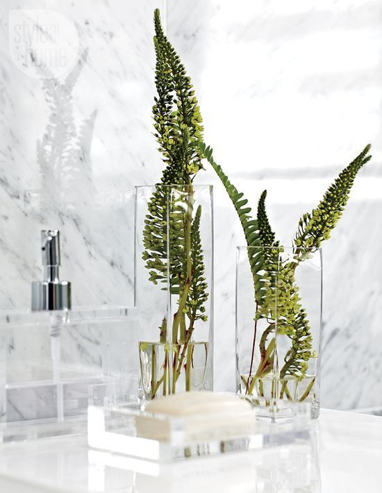glasses with fresh greenery look very laconic and easily fit a minimalist bathroom