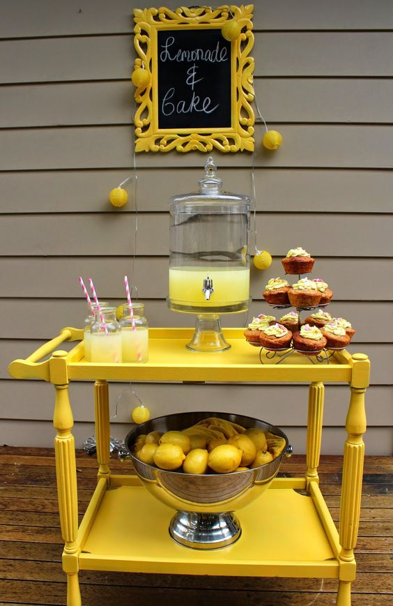 a bright yellow drink station with lemonade and a large metal bowl with lemons inside