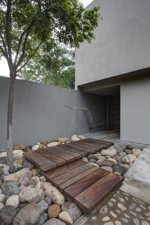 oversized rocks and pebbles and two wooden wakways placed righht on them for a Japanese-inspired space