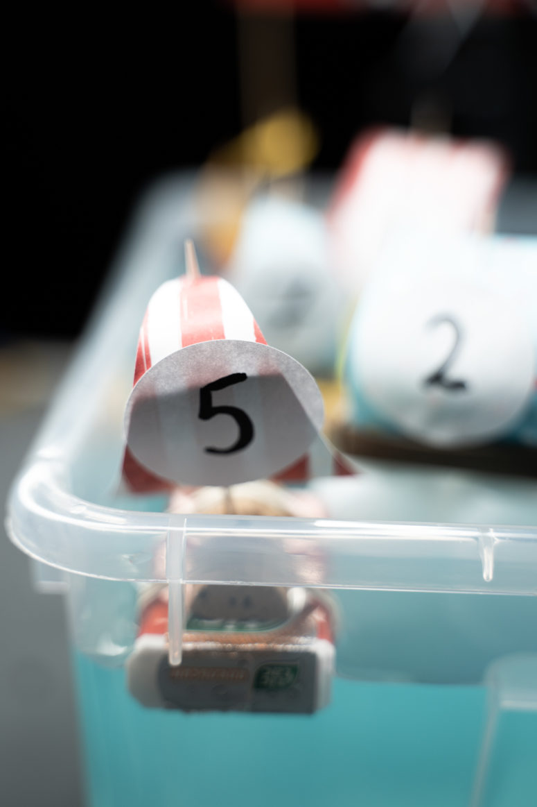 Take a wine cork, cut it in halves and attach it to a Tic Tac box using elastics, attach the sail using a toothpick again.
