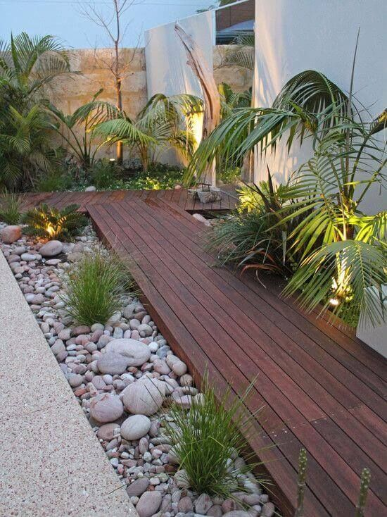 a dark stained wooden garden path with large pebbles and rocks plus some greenery and lights around