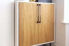 06 a Metod cabinet placed on legs and renovated with light-colored wooden doors and handles in mid-century modern style