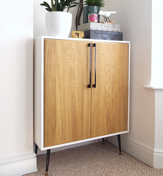 a Metod cabinet placed on legs and renovated with light colored wooden doors and handles in mid century modern style