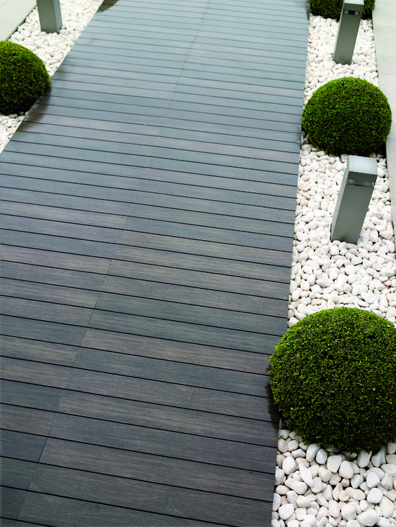 a dark stained wooden path with white pebbles lining and boxwood looks ultra-modern and bold