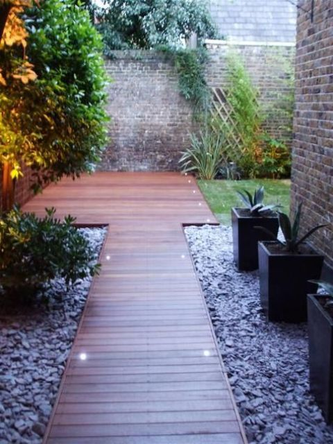 a modern and elegant wooden garden path with a matching deck surrounded with pebbles and lights along it