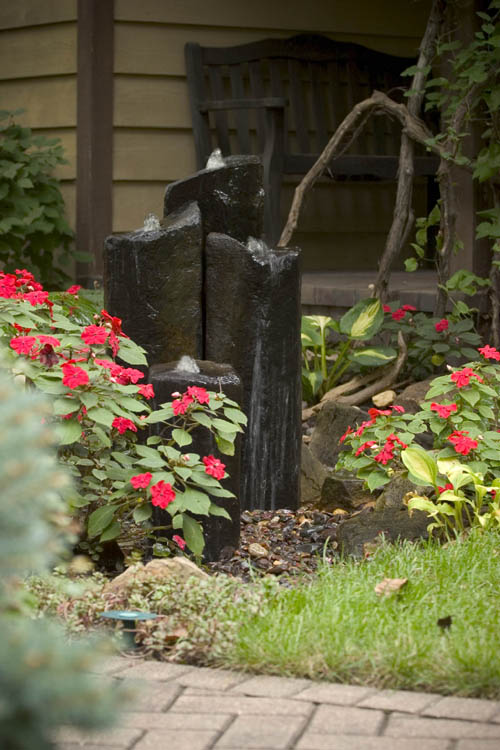 a modern fountain of large dark stones nestled in a bed of impatiens by the front door