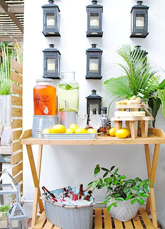 a rustic, tropical-inspired drink bar with lemons for decor, potted greenery and a boat with ice and bottles