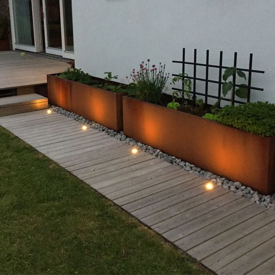 a neutral wooden garden path with a perfectly manicured lawn on one side and metal garden planters placed on pebbles on the other