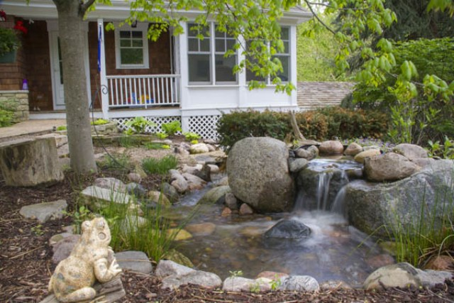 a recirculating waterfall in the front yard and a frog statuette to mark the outdoor space