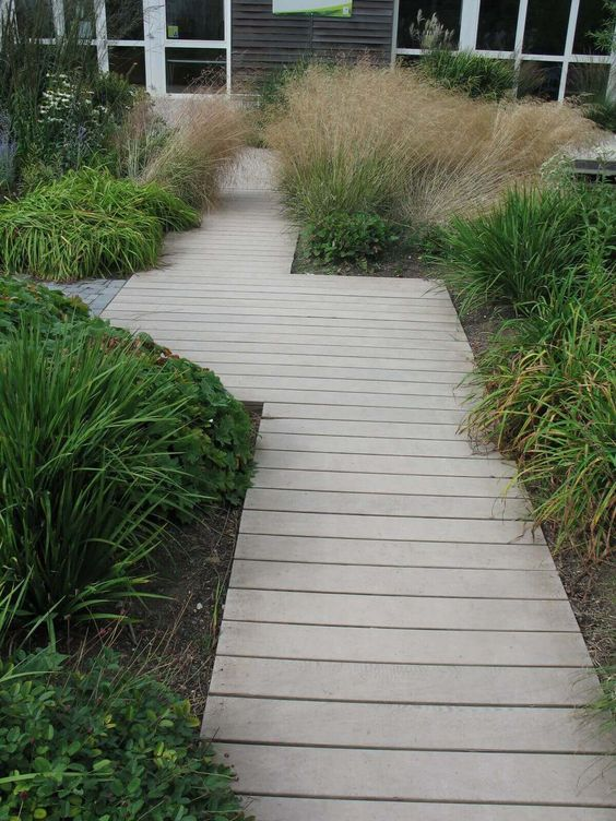 a neutral wooden plank path surrounded with shrubs and greenery for a beach cottage garden