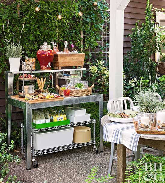 an outdoor metal station with a shelf, with potted greenery, drinks and appetizers for a party