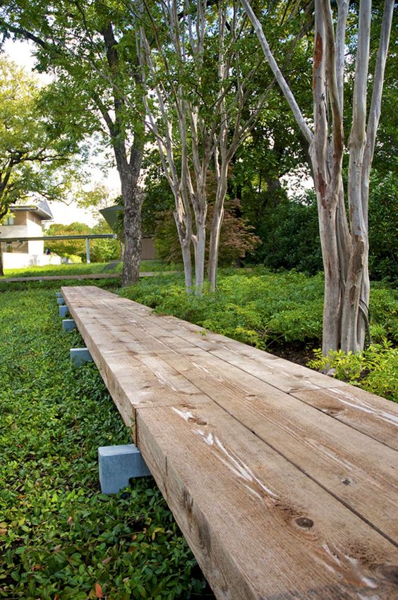 a raised wooden pathway is a comfortable and welcoming idea for any modern garden