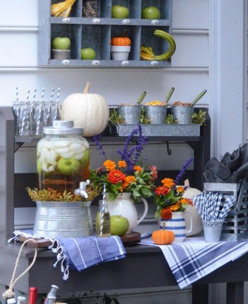 a rustic meets vintage drink bar with pumpkins and apples and bold fall blooms plus drinks