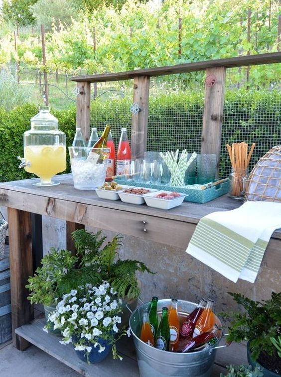 a rustic meets vintage drink station with potted greenery and blooms and a wire backdrop plus a bucket with bottles