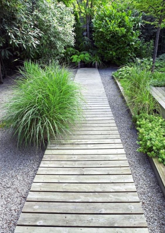 a simple whitewashed wood garden path placed on usual gravel looks laconic, simple and casual