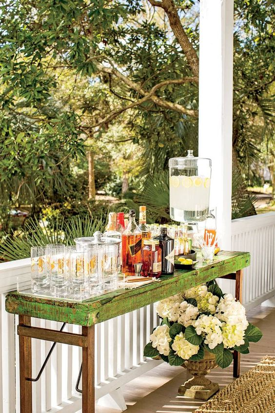 a rustic shabby chic drink station in green and stain with glasses and drinks is a stylish idea