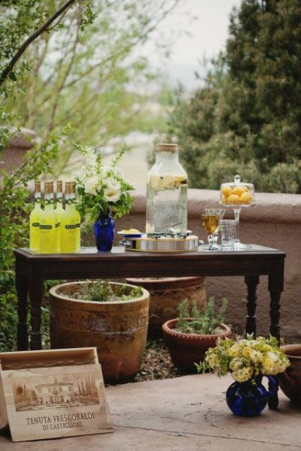 a rustic vintage drink station with potted greenery, bottles with lemonade and a vase with blooms