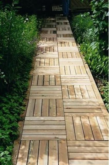a wooden garden path done with stripes in different directions is a stylish and catchy idea