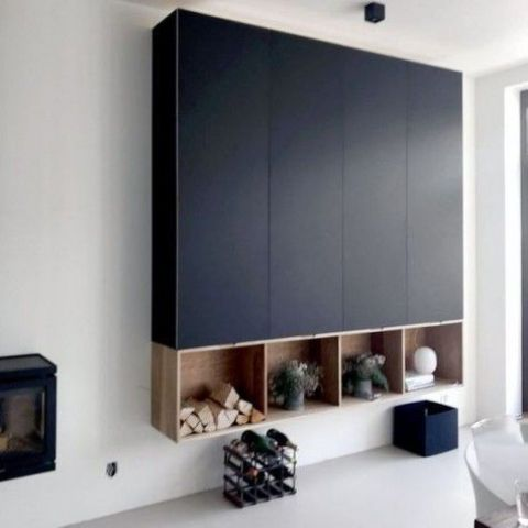 a large black storage unit built of several IKEA Metod cabinets and some open storage boxes underneath looks very contemporary