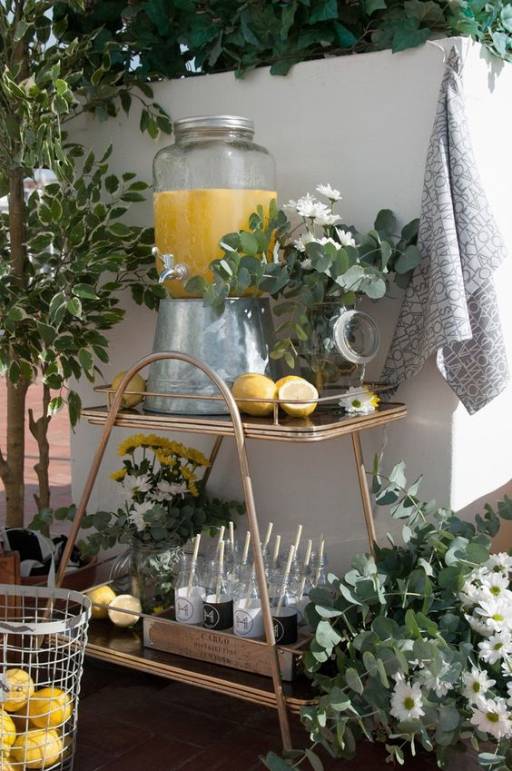 a stylish plywood and metal drink station with white and yellow blooms in vases and lemonade and bottles