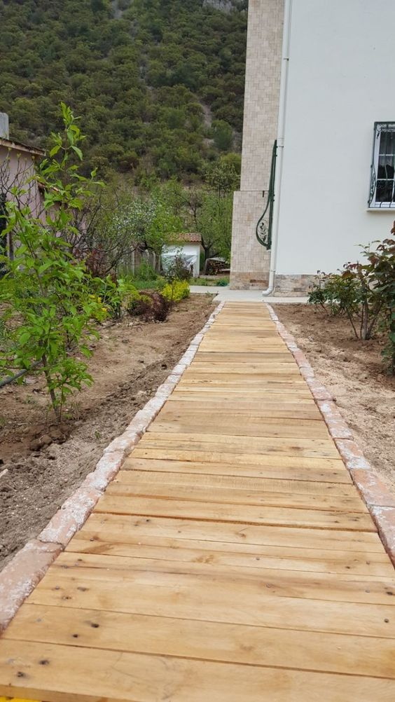 a wooden walkway with a stone border is a cool rustic idea for many outdoor spaces and is easy to construct