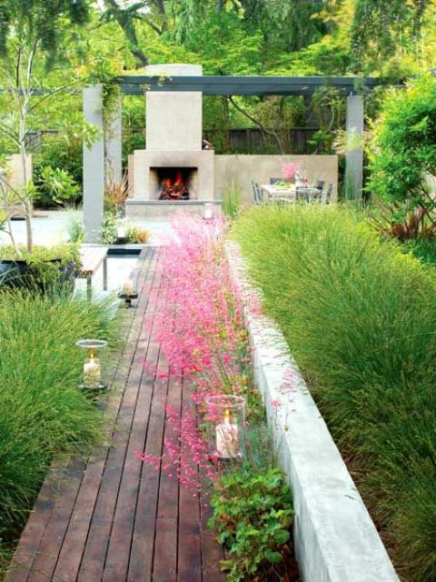 a stained wooden path lined up with candles and with greenery and bright blooms for a modern garden