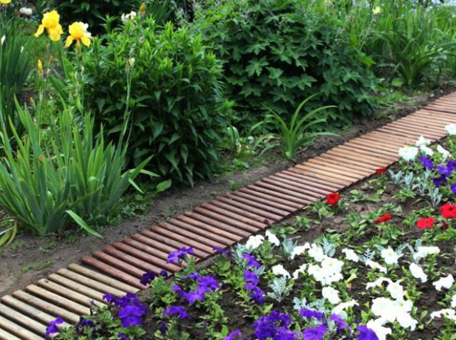a simple and cute garden path made of pallet wood and painted in different colors