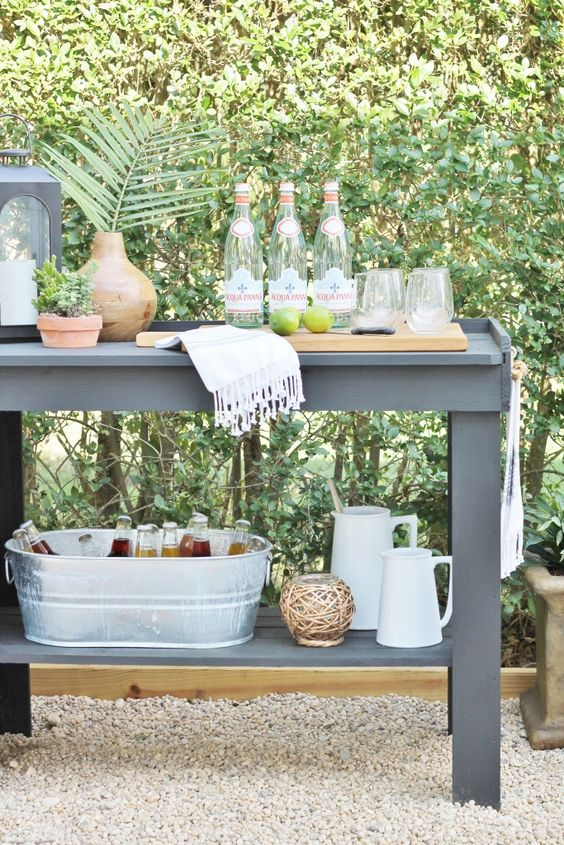a vintage-inspired wooden drink station painted grey, with a grey lantern, some jugs and a candle holder