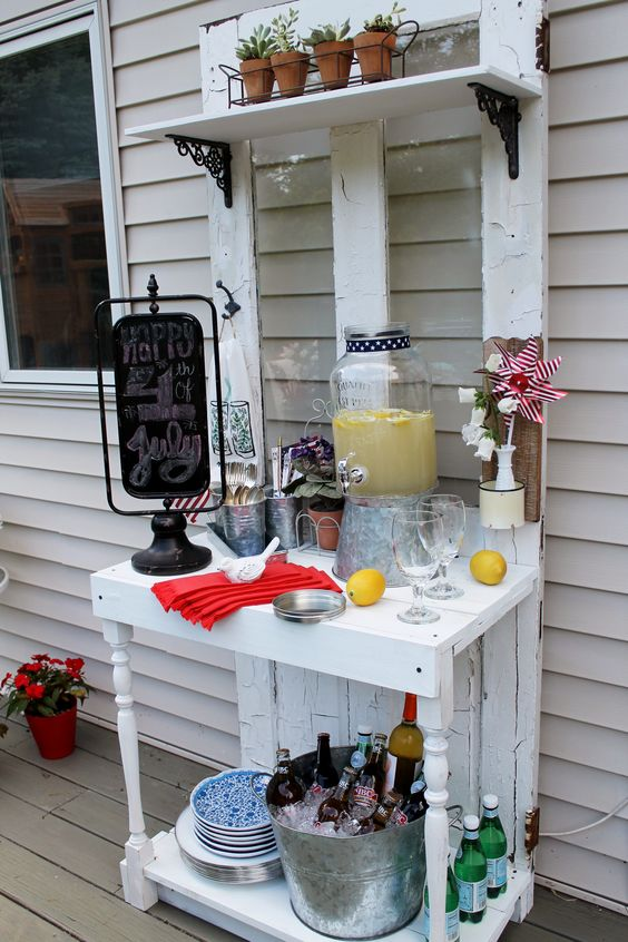 a white vintage-inspired drink station with potted greenery, some bottles in a bucket with ice cubes and a chalkboard sign