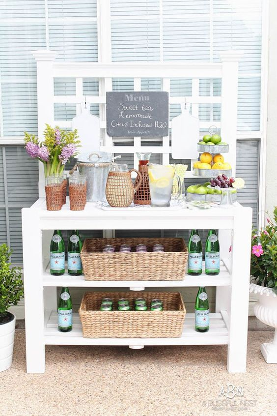 an outdoor drink station of a large table with shelves, baskets, vases and a chalkboard menu