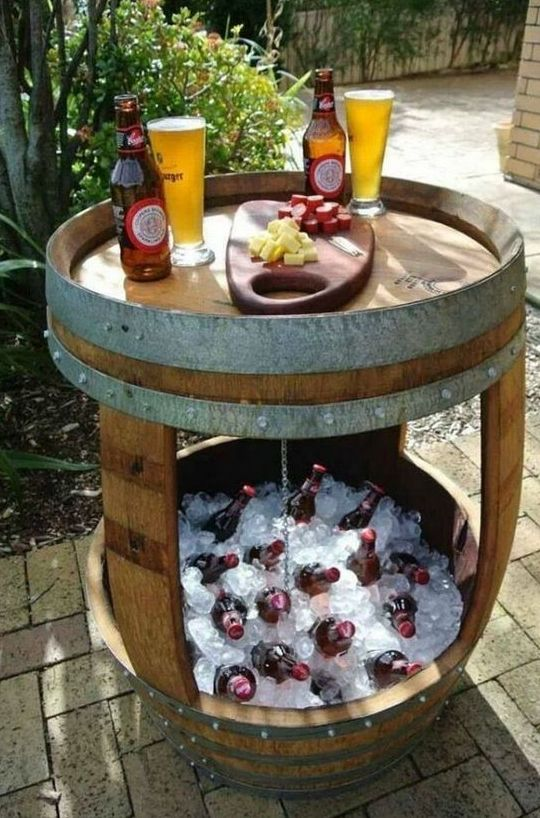 a large barrel turned into a beer drink station with a cooler, bottlers and appetizers on top