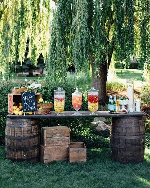 a rustic party bar of two barrels and a large shelf plus crates under iit, with fruits and glass tanks with fruits and lemonades