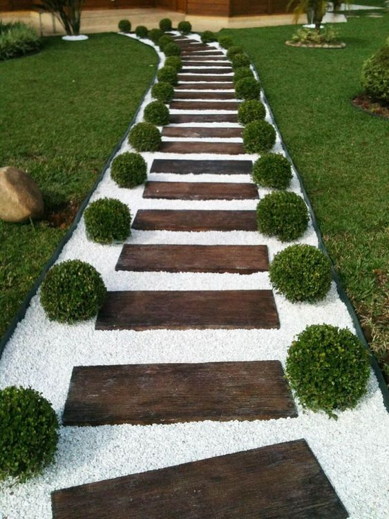 a stained wood garden path with white gravel and boxwood looks very formal, elegant and inviting