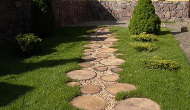a wood slice garden path mixed up with gravel and a lawn around for a rustic feel