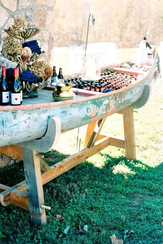 a vintage canoe boat turned into a drink station on stands can accommodate a lot of drinks and appetizers