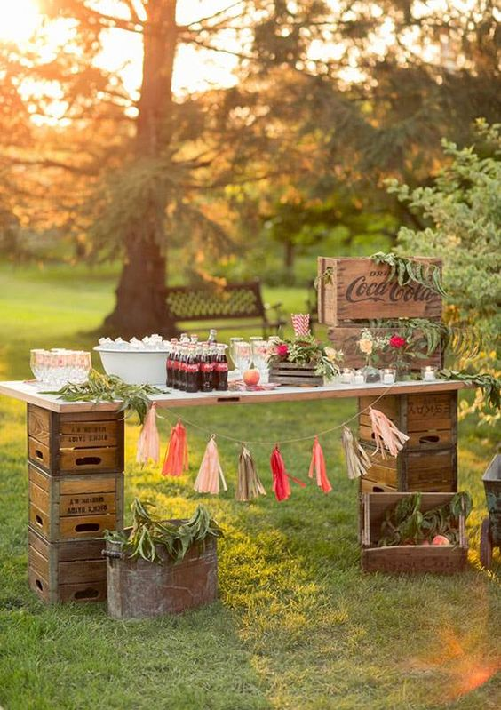 a vintage industrial drink station built of crates and a tabletop, decorated with greenery and a colorful tassel garland