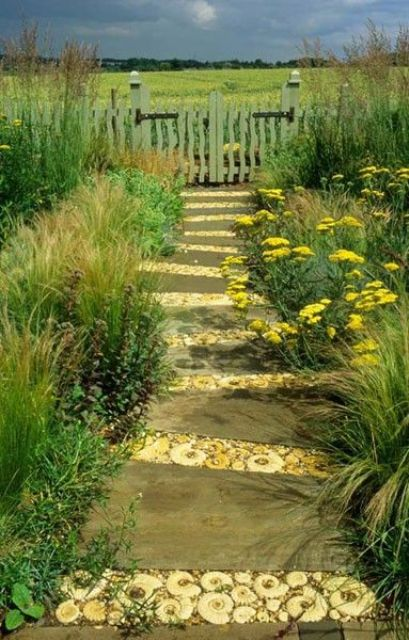 a wooden and sea shell garden path lined up with greenery and bright blooms is ideal for a beach garden