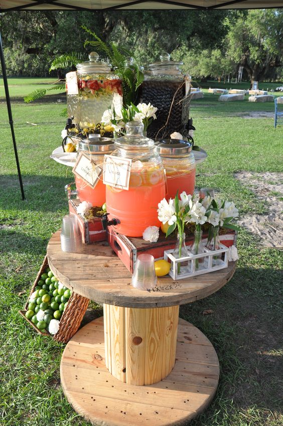 an oversized wooden spool as a drink bar, with a basket with limes and lemonades and blooms in vases