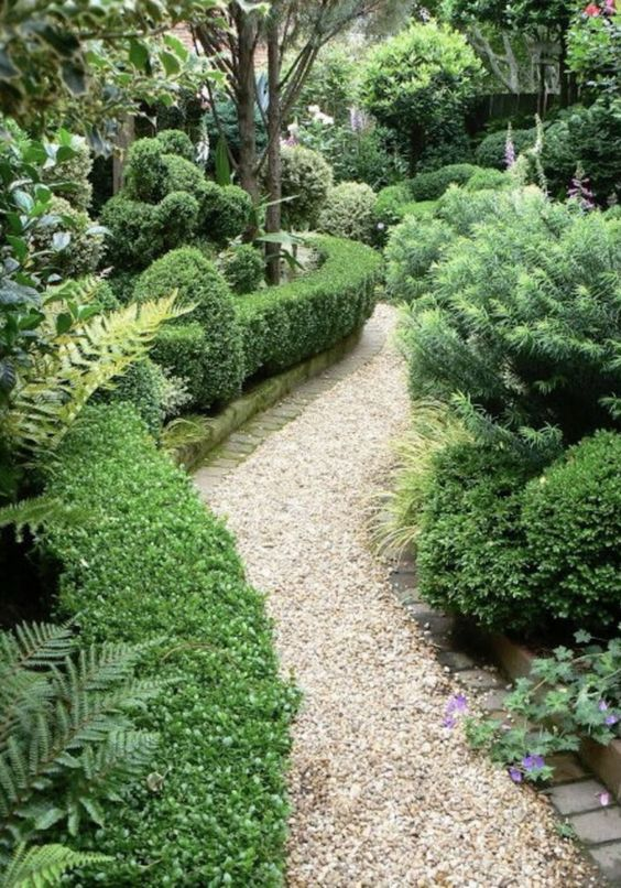 a chic neutral-colored gravel pathway with brick lining in a lush garden is a cool idea that allows drainage