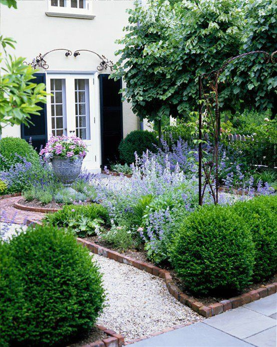 a classic small garden with garden beds lined with bricks and white gravel paths that are manicured and are very neat