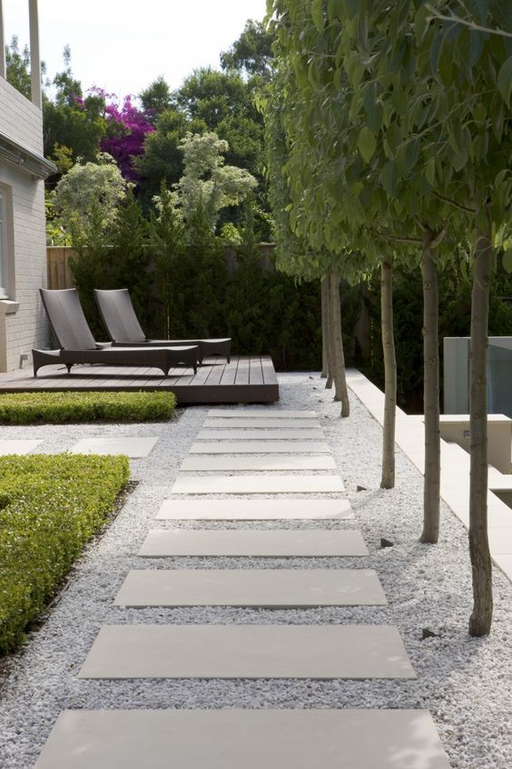a formal outdoor space with a gravel and long paving stones plus a wooden deck and trees lining the path