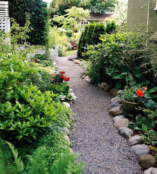 a gravel garden path lined with large rocks that help to keep the gravel in place and add a wild look