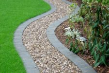a gravel gardne path lined with bricks to keep gravel in place and make it look neat